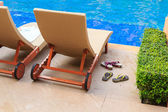 Chaise lounges in swimming pool — Stock Photo