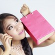 Shopping woman talking on the phone and holding bag — Stock Photo
