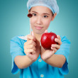 Female dentist holding an apple and  metal medical equipment too — Stockfoto