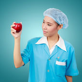 Female dentist holding an apple and metal medical equipment too — Stock Photo