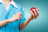Kobieta dentysty trzyma jabłko i strzykawki do zębów dentystycznych ca — Zdjęcie stockowe