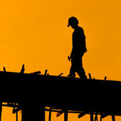 Silhouette of construction workers on scaffold working under a h — Stock Photo