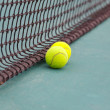 Tennis Ball on the Court Close up with Net in the Background — Stock Photo