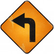 Turn left road sign. Damaged yellow metallic road sign with turn — Stock Photo #35885471