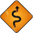 Winding road sign. Damaged yellow metallic road sign with windin — Stock Photo
