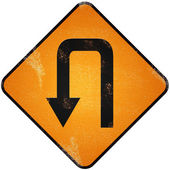 U turn road sign. Damaged yellow metallic road sign with U turn — Stock Photo