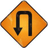 U turn road sign. Damaged yellow metallic road sign with U turn — Stock Photo