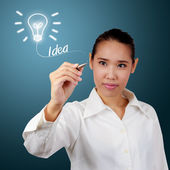 Business Woman writing idea word under lamp symbol. For business — Stock Photo