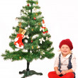 Stock Photo: Little girl decorate christmas tree