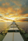 Cargo ship underway at sunset — Stock Photo