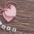 Royalty-Free Stock Photo: Pink hearts on wooden board with pink ribbon and letters