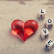 Royalty-Free Stock Photo: Red heart on wood with a word love