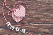 Pink hearts on wooden board with pink ribbon and letters — Stock Photo