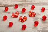 Red hearts on wooden board with red plastic roses — Stock fotografie