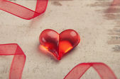 Red heart on wooden board with red ribbon — Stock Photo