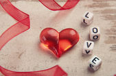 Red heart on wooden board with a word love — Stok fotoğraf