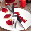 Setting table for valentine's day with petals — Stock Photo