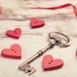 Red wooden hearts on wooden board with key and ribbon — Stock Photo