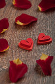 Roses petals on wooden board with hearts — Stock Photo
