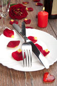 Setting table for valentine's day with petals — Stockfoto