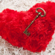 Red toy heart on white paper wih the key — Stock Photo #18560353