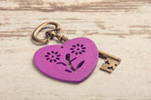 Violet wooden heart on wooden desk with key and ribbon — Stok fotoğraf