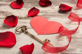 Red heart on wooden desk with key — Stock Photo