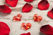 Red hearts on the wooden board with petals — Stock Photo