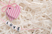 Pink hearts on white paper with letters love — Stock Photo