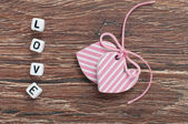 Pink hearts on wooden board with letters love — 图库照片
