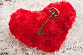 Red toy heart on white paper wih the key — Stockfoto