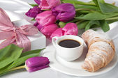 Breakfast with coffee and croissant, gift box and tulips on white silk — Stock Photo