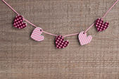 Five hearts on wooden background — Stock Photo
