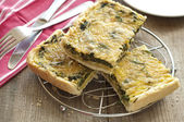 Tasty quiche with spinach and parmesan in the pan — Stock Photo
