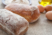 Homemade bread ciabatta on the table. Olive oil, eggs and flour — Stock Photo