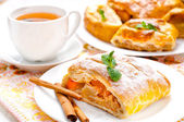 Slice of an apple strudel with tea — Stock Photo