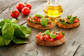 Italian bruschetta with chopped vegetables, herbs and oil on gr — Stock Photo