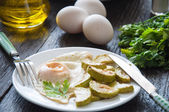 Fried eggs and chopped zucchini with parsley on the plate — Stock Photo