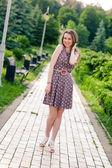 Beautiful young woman walking along the road in summer park — Foto de Stock
