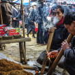 Lighting and smoking tobacco in traditional long pipes at Sunday market. — Stock Photo