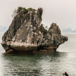 Lone rowboat travels in front of spectacular limestone rock — Stock Photo