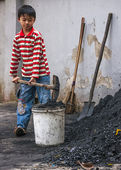 Boy scoops coal in bucket to take inside home. — Stock Photo