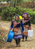 Two Hmong women loaded up baskets on their backs come around the bend in the road. — Stock Photo