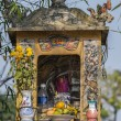 Stock Photo: Vietnam: Small shrine along road with cute painting, flowers