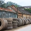 Vietnam: Line of retired truck tires along village road. — Stock Photo