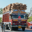 图库照片: Nagaur in RajasthIndi- February 2011 - Overloaded dump truck filled with jute bags on road.