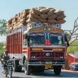 Foto Stock: Nagaur in RajasthIndi- February 2011 - Overloaded dump truck filled with jute bags on road.
