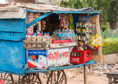 Indian city of Agra - February 2011 - Street vendor sells basic grocery products in a typical small booth on wheels. — Stock Photo