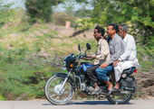 Rajasthan in India - February 2011 - Typical view of three guys, actually three generations, on one motorbike and all without helmets. — Stock Photo