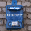 Stock Photo: RussiUglich - 27 August 2010 - Blue Post Office box as receptacle for outgoing mail against wall in street.